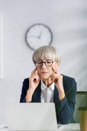Photo pour Chef d'équipe concentré dans les lunettes regardant ordinateur portable sur le bureau - image libre de droit