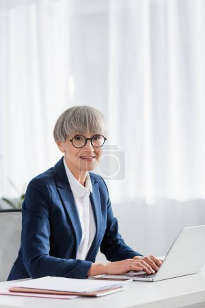 cheerful team leader in glasses smiling while using laptop on desk