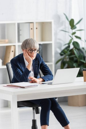 gelangweilte Teamleiterin mit Brille blickt auf Laptop auf Schreibtisch in modernem Büro
