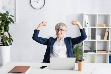 Photo for Cheerful team leader in glasses celebrating triumph in office - Royalty Free Image