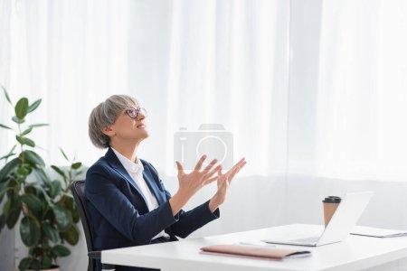 líder del equipo insatisfecho en gafas de gestos mientras mira hacia arriba en la oficina