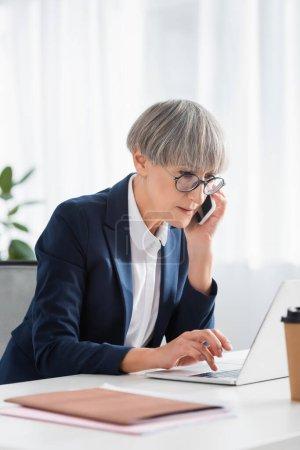 Photo pour Femme d'affaires d'âge moyen dans des lunettes parler sur smartphone tout en utilisant un ordinateur portable - image libre de droit