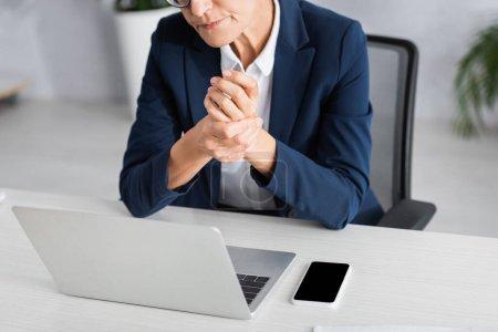 Foto de Vista recortada del líder de equipo de mediana edad cerca de dispositivos en el escritorio - Imagen libre de derechos