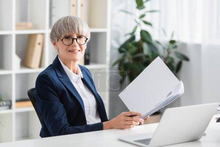 Photo pour Heureux chef d'équipe dans les lunettes tenant dossier avec des documents près de l'ordinateur portable sur le bureau - image libre de droit