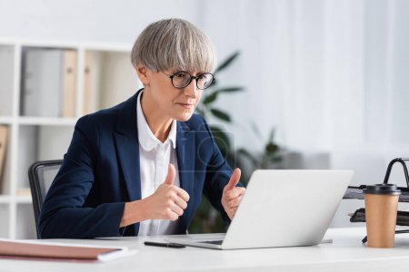 mature team leader in glasses showing thumbs up while looking at laptop