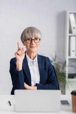 Photo pour Heureux chef d'équipe d'âge moyen dans les lunettes pointant du doigt et regardant la caméra - image libre de droit