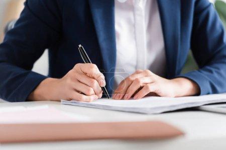 vue recadrée du chef d'équipe signant les documents sur le bureau