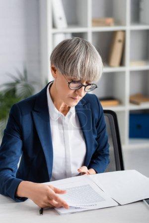 chef d'équipe d'âge moyen en lunettes regardant contrat dans le dossier