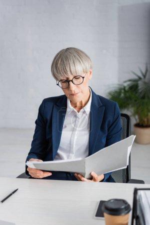 Photo pour Chef d'équipe d'âge moyen en lunettes regardant le dossier avec des documents près de tasse en papier sur le premier plan flou - image libre de droit