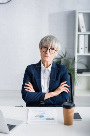 middle aged businesswoman in glasses sitting with crossed arms near charts and graphs on desk