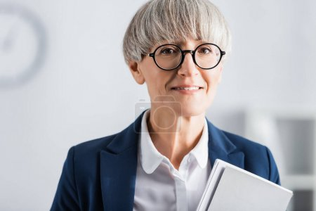 happy middle aged team leader in glasses and suit with folder