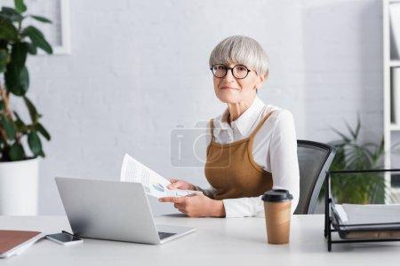 Photo pour Mature chef d'équipe assis au bureau et tenant des papiers avec des graphiques et des graphiques dans le bureau - image libre de droit
