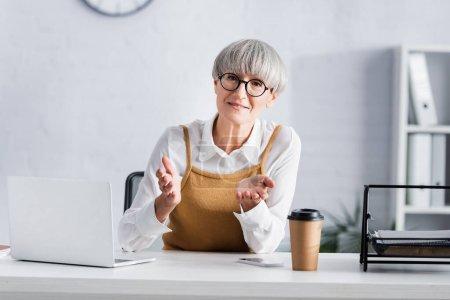 Photo pour Chef d'équipe d'âge moyen en lunettes gestuelle tout en regardant la caméra près de gadgets sur le bureau - image libre de droit