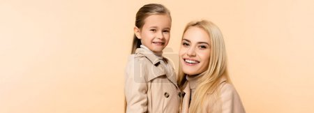 Photo for Cheerful blonde mother and daughter isolated on beige, banner - Royalty Free Image