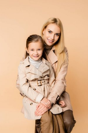 Photo for Cheerful blonde mother hugging happy daughter isolated on beige - Royalty Free Image