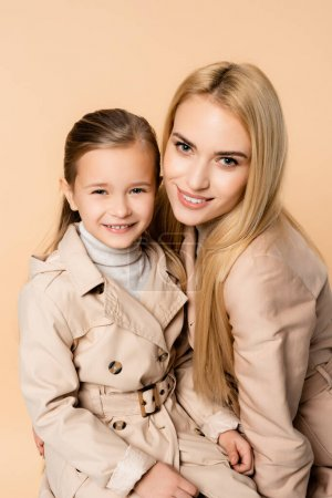 Photo for Cheerful blonde mother and happy daughter looking at camera isolated on beige - Royalty Free Image