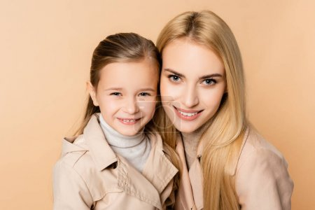 Photo for Cheerful blonde mother and happy daughter in coats looking at camera isolated on beige - Royalty Free Image