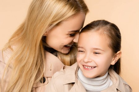 Photo for Cheerful blonde mother and happy daughter laughing isolated on beige - Royalty Free Image