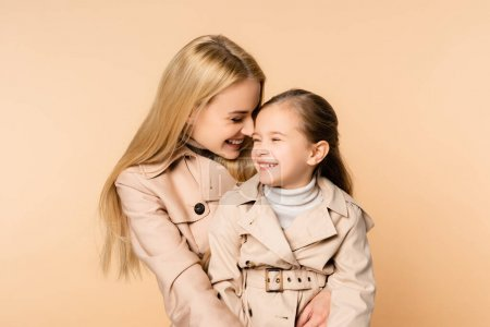 Photo for Joyful blonde mother hugging happy daughter in trench coat isolated on beige - Royalty Free Image