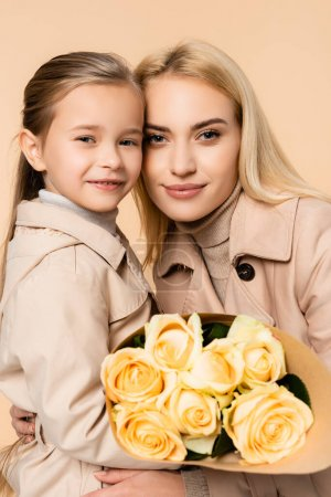 Photo for Joyful kid holding roses near cheerful mother on 8 march isolated on beige - Royalty Free Image