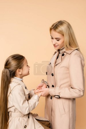 Photo for Mother and daughter holding hands and look at each other isolated on beige - Royalty Free Image