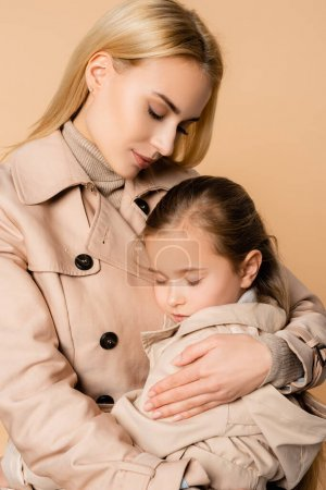 Photo for Blonde mother embracing daughter with closed eyes isolated on beige - Royalty Free Image