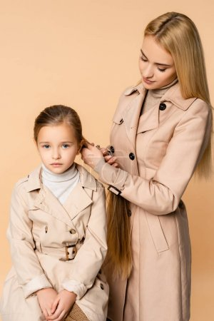 Photo for Blonde mother weaving braid on daughter isolated on beige - Royalty Free Image