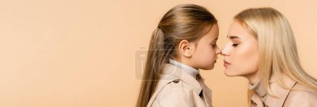 Photo for Side view of mother and kid touching noses isolated on beige, banner - Royalty Free Image
