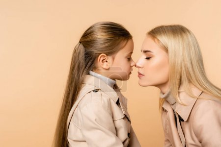 Photo for Side view of mother and kid touching noses isolated on beige - Royalty Free Image