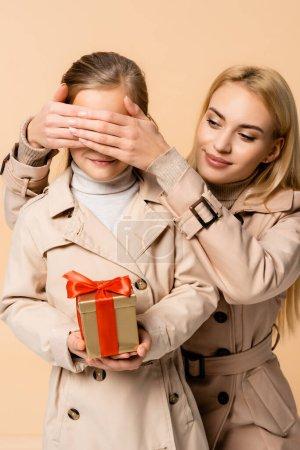 fröhliche Mutter bedeckt Kinderaugen mit Geschenkschachtel isoliert auf beige
