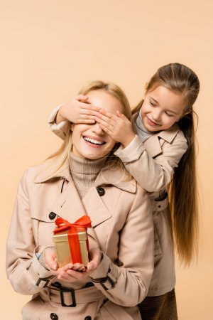 Photo for Kid covering eyes of happy mother with present isolated on beige - Royalty Free Image