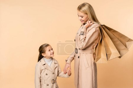 Photo for Happy mother with paper bags holding hands with kid isolated on beige - Royalty Free Image