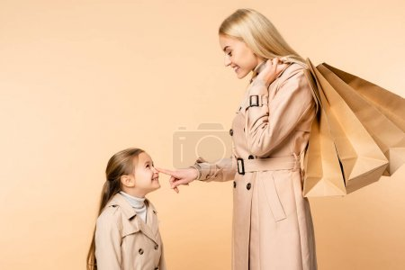 Photo for Happy mother holding paper bags and touching nose of kid isolated on beige - Royalty Free Image