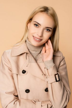 blonde woman in trench coat smiling and looking at camera isolated on beige
