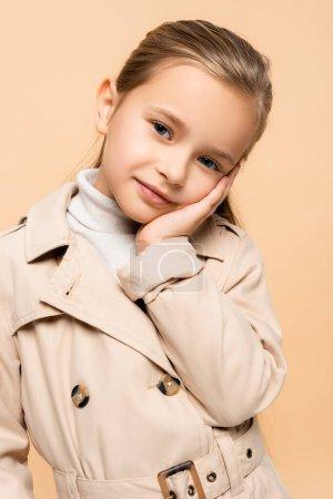 Photo pour Heureux enfant en trench coat regardant caméra isolé sur beige - image libre de droit