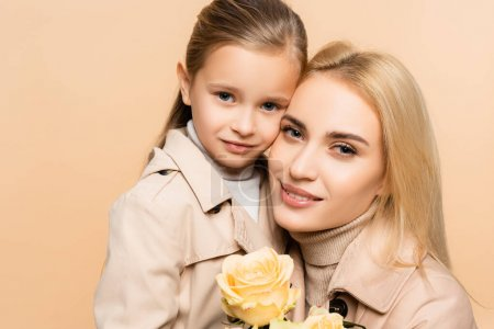 Photo for Joyful mother holding flowers and hugging daughter isolated on beige - Royalty Free Image