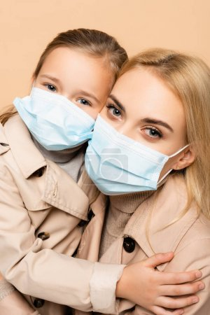 Photo for Mother and daughter in medical masks looking at camera isolated on beige - Royalty Free Image