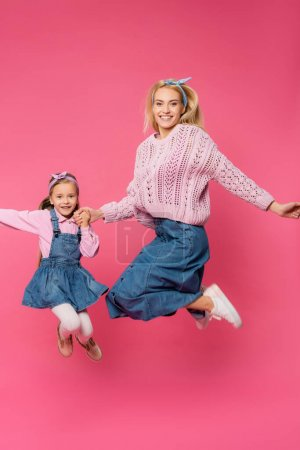 Photo for Full length of mother and kid smiling and jumping on pink - Royalty Free Image
