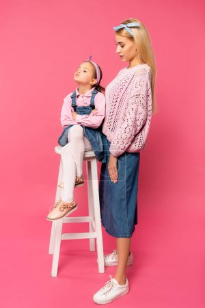 Photo for Full length of mother looking at offended kid sitting on chair on pink - Royalty Free Image