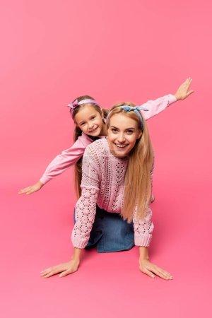 mère souriant près de fille avec les mains tendues sur rose