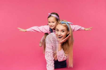 Photo for Mother smiling near daughter with outstretched hands isolated on pink - Royalty Free Image