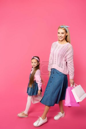 happy mother and daughter walking with shopping bags on pink