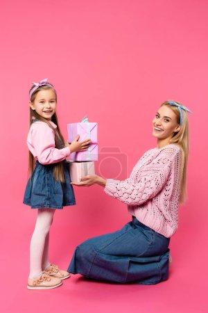 Photo pour Mère heureuse souriant près de fille tenant des cadeaux sur rose - image libre de droit