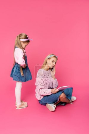offended kid looking at mother talking on smartphone and using digital tablet on pink