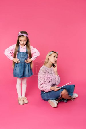 offended kid standing with hands on hips mother talking on smartphone and using digital tablet on pink