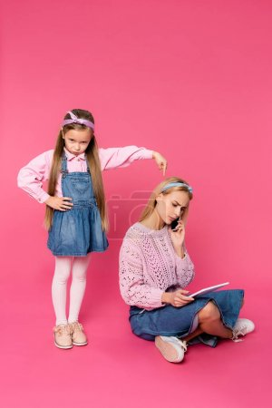 offended kid pointing with finger at mother talking on smartphone and using digital tablet on pink