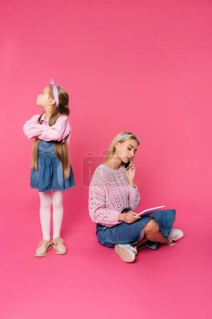 offended kid looking away while standing with crossed arms near mother talking on smartphone and using digital tablet on pink
