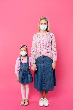 longitud completa de la madre y la hija en máscaras médicas de pie y tomados de la mano en rosa