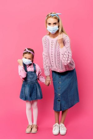 Photo for Full length of mother and daughter in medical masks showing clenched fists and holding hands while standing on pink - Royalty Free Image