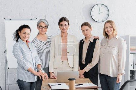 Photo pour Heureux femmes d'affaires multiculturelles près du lieu de travail pendant le séminaire - image libre de droit